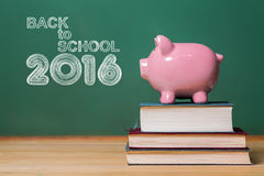 Back to School 2016 text with pink piggy bank on top of books Royalty Free Stock Image