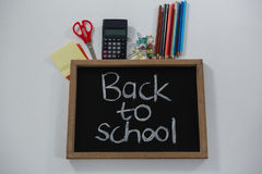 Back to school text on slate with various supplies. Overhead view of back to school text on slate with various supplies Royalty Free Stock Photo