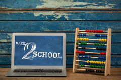 Composite image of back to school text on white background. Back to school text on white background against laptop by abacus on table stock illustration