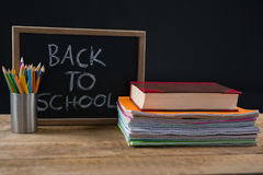 Back to school text written on chalkboard with book stack and pen holder. Close-up of back to school text written on chalkboard with book stack and pen holder Royalty Free Stock Image