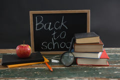 Back to school text written on chalkboard with various stationery and apple. Close-up of back to school text written on chalkboard with various stationery and Stock Photos
