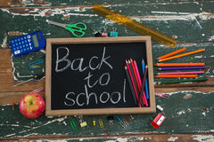 Back to school text written on chalkboard with various stationery and apple. Close-up of back to school text written on chalkboard with various stationery and Royalty Free Stock Image