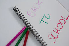 Back to school text written on spiral book. Close-up of back to school text written on spiral book Stock Images