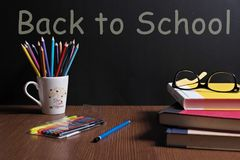 BACK TO SCHOOL. Textbooks, pencil tray, eyes glasses , color pen are on the table in front of a black board Royalty Free Stock Photography