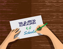Back to school. Themed concept design. Hands writing phrase  on the paper. Stock  in flat Royalty Free Stock Photos