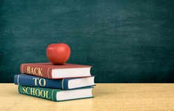 Back to school. Three books with text: back to school and a red apple, chalkboard on background with empty space (3d render Stock Image