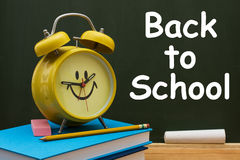 Back to School Time. Book with pencil and eraser with a retro alarm clock  in front of a chalkboard, Back to School Time Royalty Free Stock Photography