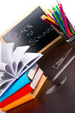 Back to school time. Back to school sign on a blackboard with books and pencils Stock Photos