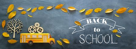 Back to school. Top view banner of cardboard school bus with wooden gears as concept of success and achievement next to autumn dry. Leaves over classroom royalty free stock images