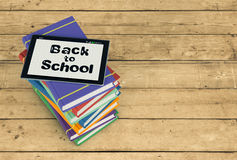 Back to school. Top view of a stack of books with a tablet pc and text: back to school, wooden background, empty space at the right of the image (3d render Royalty Free Stock Image