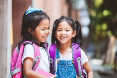 Two cute asian child girls with school bag holding a book and talking together in the school royalty free stock image