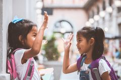Two cute asian child girls with school bag playing together after school in the school stock photos