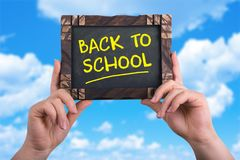 Back to school. A woman holding chalkboard with words back to school on blue sky background Royalty Free Stock Photo