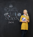 Back to school woman teacher smiling by blackboard. Young female blonde teacher smiling against blackboard Royalty Free Stock Images