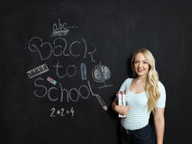 Back to school woman teacher smiling by blackboard Stock Image