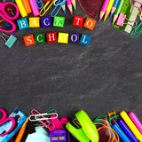Back to School wooden blocks with school supplies frame on blackboard Stock Photography