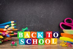 Back to School wooden blocks with supplies on a chalkboard background Stock Images
