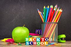 Back to School wooden blocks with supplies on a chalkboard background Royalty Free Stock Image