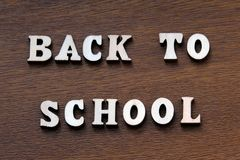 Back to school. Wooden letters on a brown background. royalty free stock photos