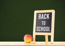 Back to school word on blackboard on wood table with apple at gr Stock Photography