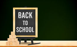 Back to school word on blackboard on wood table with pyramid cub Royalty Free Stock Photos