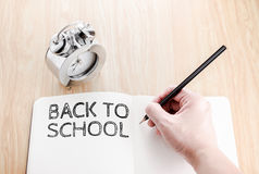 Back to school word on book with hand writing and alarm clock on Royalty Free Stock Image