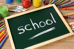 Back to school, word written in chalk on small blackboard, classroom, school desk Royalty Free Stock Photos