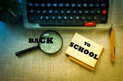 BACK TO SCHOOL wording on notebook with typewriter ,pen and magnifying glass on wooden table. Stock Photos