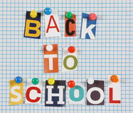 Back To School. The words Back To School in cut out magazine letters pinned to a background of blue lined graph paper Stock Images