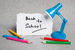 Back to school words with little lamp and pencils. On gray background Royalty Free Stock Images