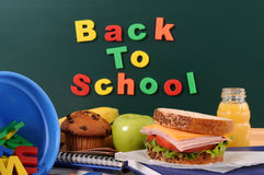 Back to school words text on classroom blackboard with packed lunch Royalty Free Stock Photos