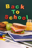 Back to school words text on classroom blackboard with packed lunch, vertical Stock Photos