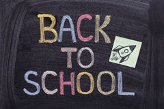 Back to school writing on blackboard with paper note with a rock. Et on it. Close up Royalty Free Stock Image