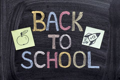 Back to school writing on blackboard with paper notes with a roc. Ket on it and apple. Close up Stock Image