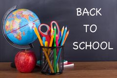 Back to School Writing on a Blackboard. `Back To School` text written on a chalkboard with school accessories on a wooden desktop Royalty Free Stock Photography