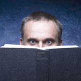 Back to school written on black book. Mature man behind book on blue background. Royalty Free Stock Photos