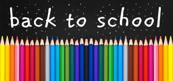 Back to school written on black chalkboard with colorful wooden pencils. Back to school written on black chalkboard background with colorful wooden pencils Stock Photo