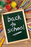 Back to school written in chalk on blackboard, school desk, vertical Stock Photo