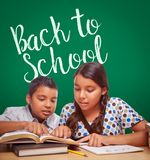 Back To School Written On Chalk Board Behind Hispanic Boy and Girl royalty free stock images
