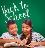 Back To School Written On Chalk Board Behind Hispanic Boy and Girl stock photography