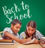 Back To School Written On Chalk Board Behind Hispanic Boy and Girl stock image