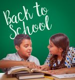 Back To School Written On Chalk Board Behind Hispanic Boy and Girl royalty free stock image