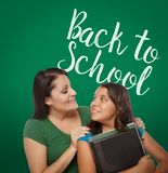 Back To School Written On Chalk Board Behind Proud Hispanic Mom. Back To School Written On Chalk Board Behind Proud Hispanic Mother and Daughter Student stock photos