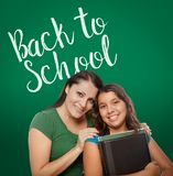 Back To School Written On Chalk Board Behind Proud Hispanic Mom. Back To School Written On Chalk Board Behind Proud Hispanic Mother and Daughter Student stock image