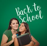 Back To School Written On Chalk Board Behind Proud Hispanic Mom. Back To School Written On Chalk Board Behind Proud Hispanic Mother and Daughter Student royalty free stock photo