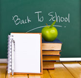 Back to school written on chalkboard. Back to school written on chalkboard with green apple and books Royalty Free Stock Photography