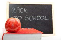 back to school written on chalkboard with apple Stock Images