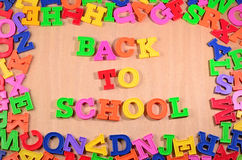 Back to school written by colorful letters on a wooden backgroun Royalty Free Stock Images