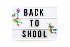Back to school written on a modern light box on white, colorful paper clips Royalty Free Stock Photography