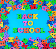 Back to school written by plastic colorful letters on a blue Stock Photos